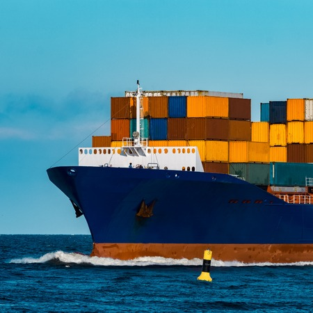Blue container ship in travel. Logistics and freight industry 写真素材