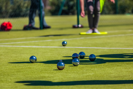 Petanque is a form of boules where the goal is to toss or roll hollow steel balls as close as possible to a small wooden ball called a jack, while standing inside a circle with Both Feet on the Ground