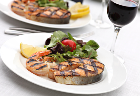 grilled fish: Grilled salmon steak with shrimps and fresh summer salad mix