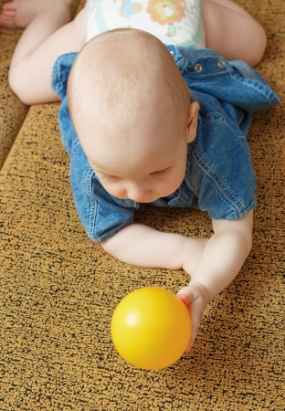 countenance: The baby holds a yellow ball lying on a yellow sofa