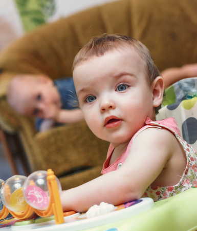 countenance: Portrait of the baby girl close-up at nursery with her brother  Stock Photo