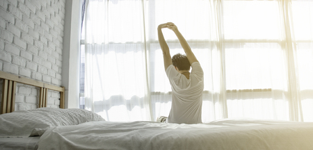 Men sit at the edge of the bed. And stretching his arms to relax in the morning.Wake up in the morning.Stretching after waking.