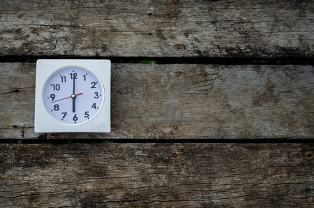 White clock on the wooden floor in the morning.On the floor there is a watch on it.