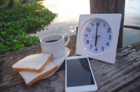 Coffee bread and White clock on a wooden table in the morning.On the river at 6:00 pm, there is a white clock on the wooden floor.Smartphone put on table.Do not focus on objects.Warm tone.