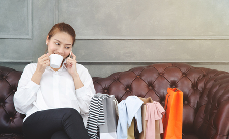 Women is talking on the phone. Beautiful Asian girl is smiling.Orange shopping bag on the sofa in the room.Girl in white shirt.