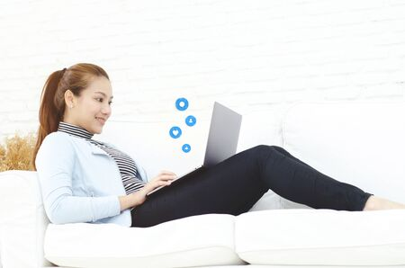 Beautiful Asian woman is smiling.Asian women work with gray laptops on the sofa in the room in the morning.She is happy to get a new job, success, or get good news.In the white room there is a woman inside.