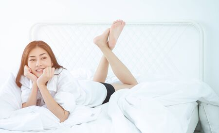 Asian women Smiled on the white futon in her bedroom.Beautiful woman smiling. 版權商用圖片