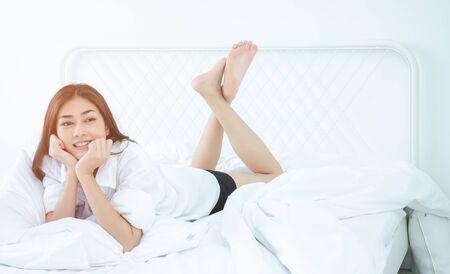 Donne asiatiche sorrise sul futon bianco nella sua camera da letto. Bella donna sorridente.