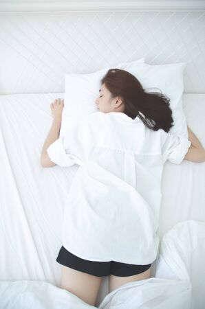 Beautiful woman sleeping in the bedroom. Woman lying face down on the bed.Girl wearing a pajama sleep on a bed in a white room in the morning.Warm tone.