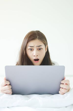 Beautiful Asian woman is smiling.Lady work with laptops on the sofa in the room in the morning.She is happy to get a new job, success, or get good news.In the white room there is a woman inside.