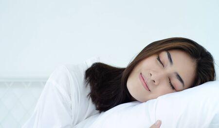 Schöne Frau, die im Schlafzimmer schläft. Frau, die mit dem Gesicht nach unten auf dem Bett liegt. Mädchen, das einen Pyjama trägt, schläft morgens auf einem Bett in einem weißen Raum. Warmer Ton.