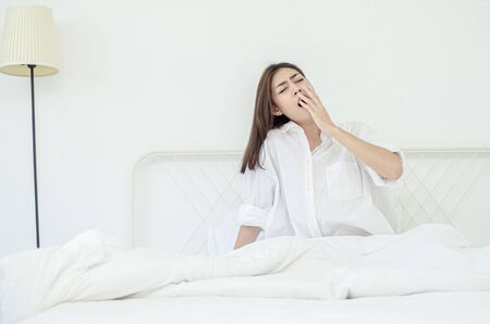 women sit at the edge of the bed. And stretching his arms to relax in the morning.Wake up in the morning. Stretching after waking.Warm tone.Do not focus on the object.