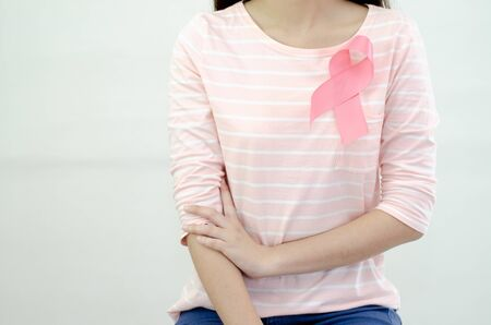 Pink ribbon affixed on an Asian woman's shirt.Do not focus on objects.World Breast Cancer Day Concept. Stock Photo