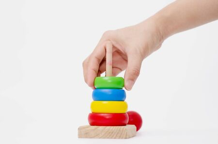 Wooden toys are red, green, yellow, and blue. Many numbers arranged beautifully.Red round wood Captured by hand.isolated a white background.Copy space.