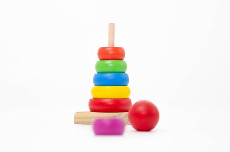 Wooden toys are red, green, yellow, and blue. Many numbers arranged beautifully. Red round wood Captured by hand. isolated a white background.Copy space.