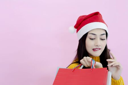 A beautiful Asian woman wearing a red Santa hat with a shopping bag.