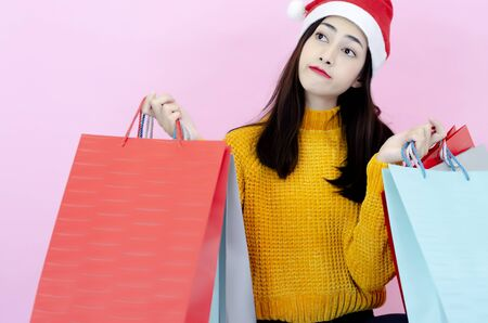 A beautiful Asian woman wearing a red Santa hat with a shopping bag. Reklamní fotografie - 135501588