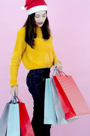 A beautiful Asian woman wearing a red Santa hat with a shopping bag. Reklamní fotografie - 135501730
