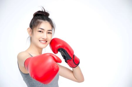 Asian Woman Wearing Red Boxing Gloves.The girl put her hands on her ears.Women are tired. Archivio Fotografico