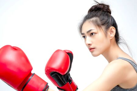 Asian Woman Wearing Red Boxing Gloves.The girl put her hands on her ears.Women are tired. 写真素材