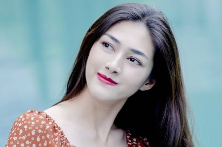 Asian woman Wearing pretty red lipstick, smiling With a green background.Sexy and cute women.
