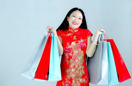 Asian woman dressed in red shopping bag. Woman smiling, she is happy. 写真素材