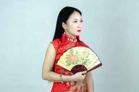 Beautiful Asian woman in a red dress holding a fan in the hand with the words of fortune and happiness in the Chinese New Year 2020, isolated on a white background.