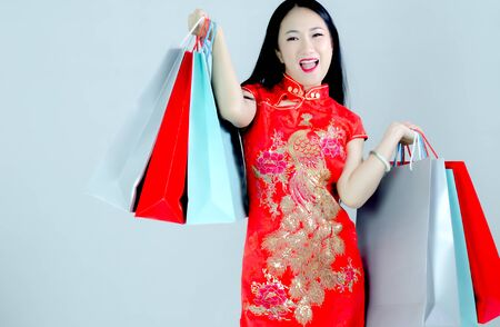 Asian women in red dresses, shopping bags. 写真素材