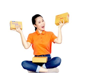 Asian women a orange shirt, blue pants, she smiled and held several brown boxes at the same time isolated white background.Happy woman successful. Copy space.