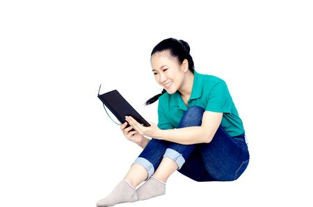Asian women wearing green shirts And gray notebook computers on a white background. Many books on the womans lap.Copy space.Do not focus on objects.