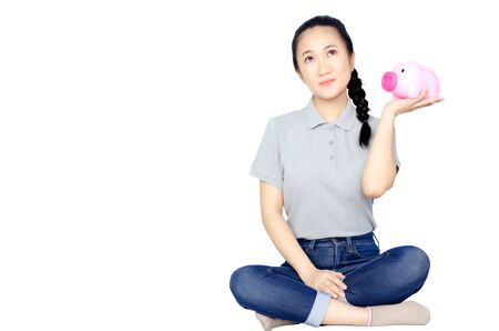 Pink pig coin jar in Asian womans hand, gray shirt.Isolated on white background. Copy space. Reklamní fotografie