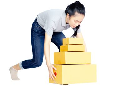 Asian women in a gray shirt, blue pants, she smiled and held several brown boxes at the same time isolated white background.Women send parcels.