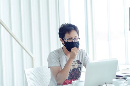 Asian Men Wearing Glasses Wearing a black mask Is working.A sick man sitting at work.In the white office there was a man in there.