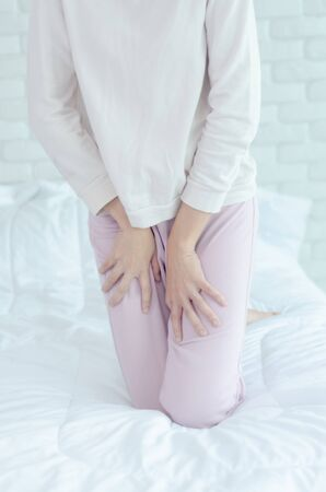 Close up Woman wearing pink pants the itching on vaginal. The woman's hand placed between her legs. She has itching at the vaginal. Stock Photo