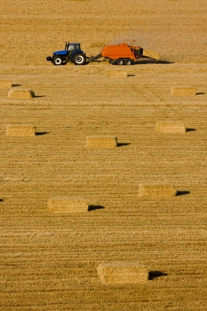 Farmers field full of hay bales with tractor Stock Photo - 8759965