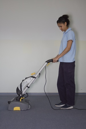 A worker is cleaning the floor with machine photo