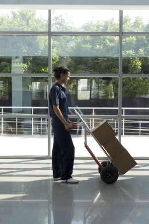 Side view of delivery woman in uniform pushing stack of cardboard boxes on dolly  Stock Photo - 10003469