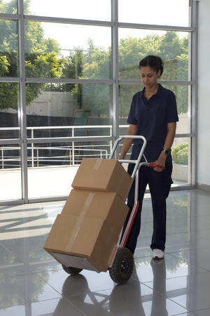 dolly: Side view of delivery woman in uniform pushing stack of cardboard boxes on dolly