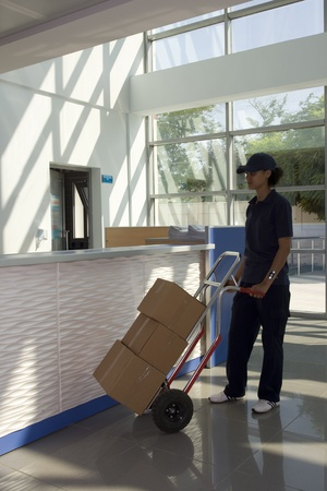Side view of delivery woman in uniform pushing stack of cardboard boxes on dolly  Stock Photo - 10004065