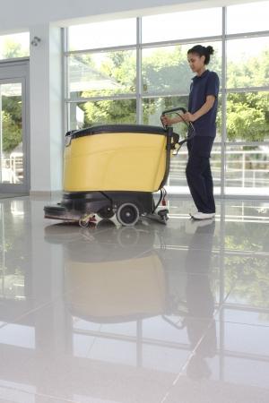limpiadores: Un trabajador est� limpiando el suelo con m�quina Foto de archivo