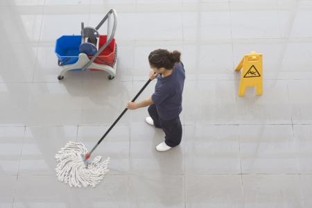 Un trabajador es limpiar el piso con el equipo Foto de archivo