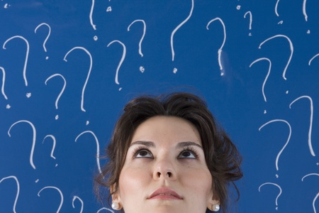 thinking people: thinking business woman in front of question marks written blackboard