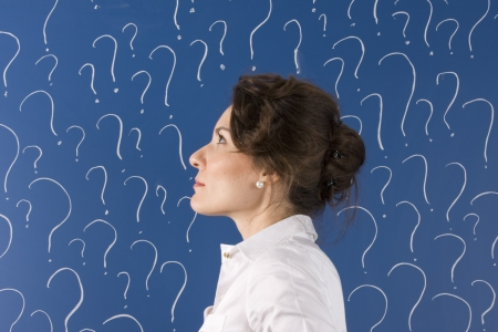 confused person: thinking business woman in front of question marks written blackboard