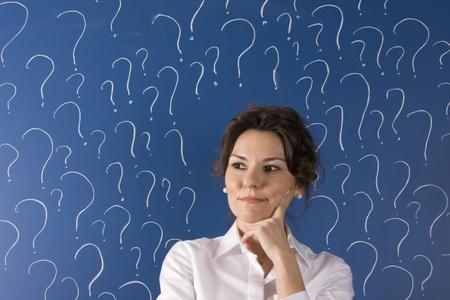 fear face: thinking business woman in front of question marks written blackboard