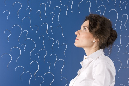 thinking business woman in front of question marks written blackboard