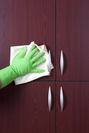 cleaner hand polishing the door of closet  photo