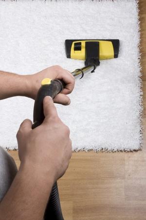 servicio domestico: Tubo de la aspiradora sobre la alfombra Foto de archivo