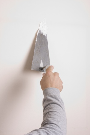 A close-up of a person stripping paint using a putty knife.  photo
