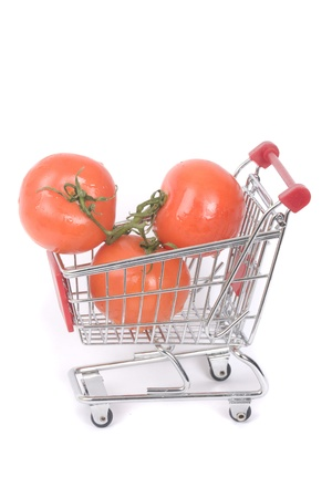 Perfect tomatoes in shopping cart on the white background  photo
