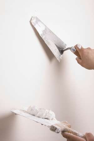 Putty Knife with Paste to repair damaged wall photo